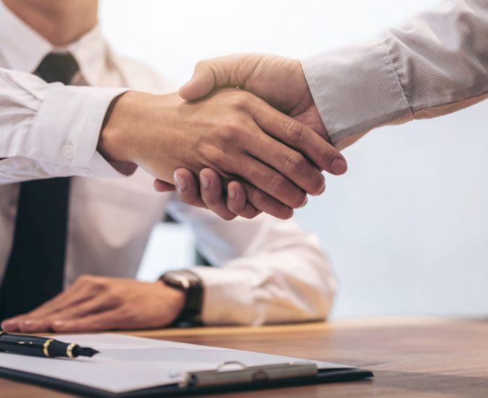 Real estate broker agent and customer shaking hands after signin